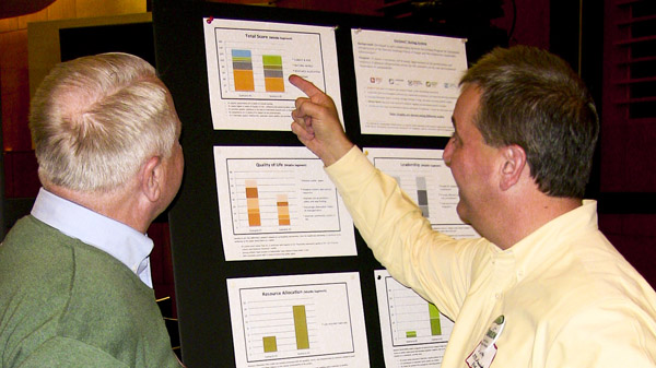 At a public meeting, two attendees compare Envision™ scores of potential project scenarios.